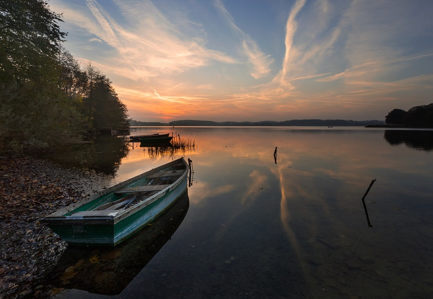 Beautiful lake landscape with fisherman boat and sunset sky. Typical polish lake in Mazury lake district. Orange sky and clouds reflected in water.