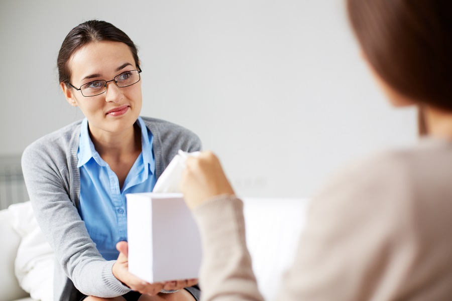 Careful psychiatrist giving box with paper tissues to her patient
