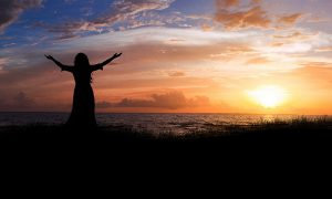 Woman raising her arms at sunrise.