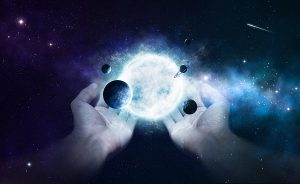 Two hands holding the sun and planets in the universe