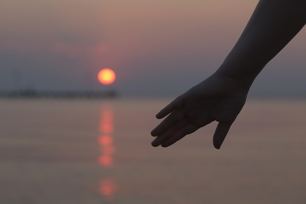 Womans hand silhouetted against an ocean sunset as the glowing orb of the sun sinks below the horizon of the water