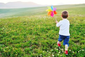 little happy child play with windmil toy and have ve fun while running on beautiful meadow at sunset