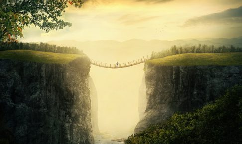 A man stands alone on a bridge between two mountains.