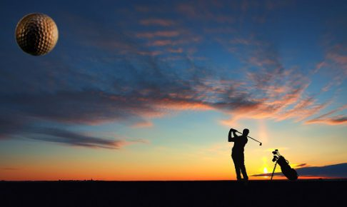 A man playing golf on sunset