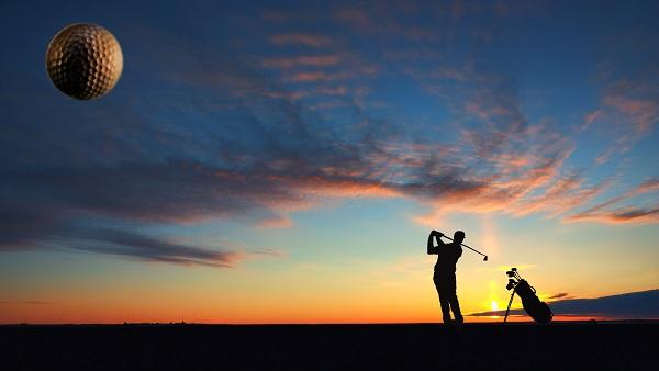 A man playing golf on sunset