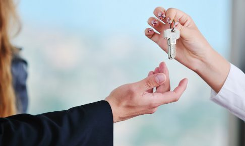 man and woman hand closeup with home keys representing buying and selling new apartment and real estate concept