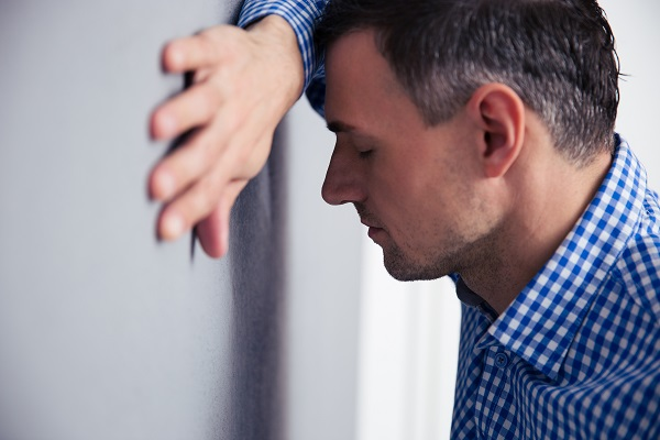 Stressed man with closed eys leaning on the gray wall