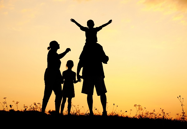 Happy family in nature at sunset