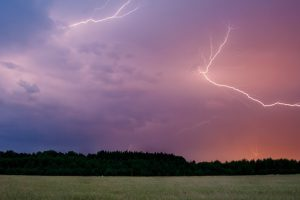 Thunderbolt over cereal field at summer time storm
