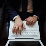 Male hands typing on laptop