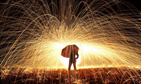 A woman holds and umbrella with fire sparks flying around her.