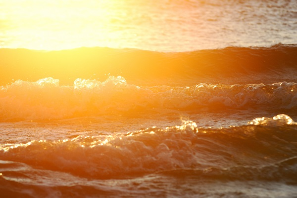 waves close-up at the sunset with bright halo