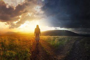 A woman walks down a path towards light.